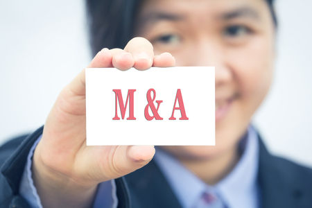merger: Businesswoman holding card with MERGER message.