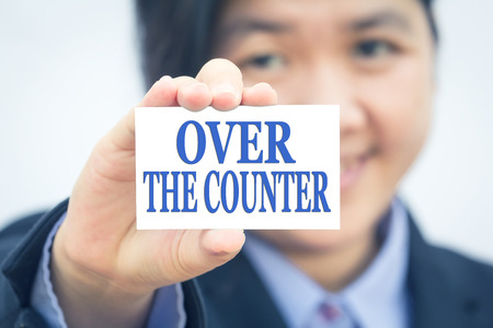 over the counter: Businesswoman holding card with OVER THE COUNTER message. Stock Photo