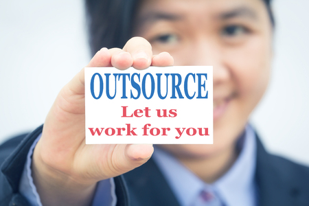 outsource: Businesswoman holding card with OUTSOURCE Let us work for you message.