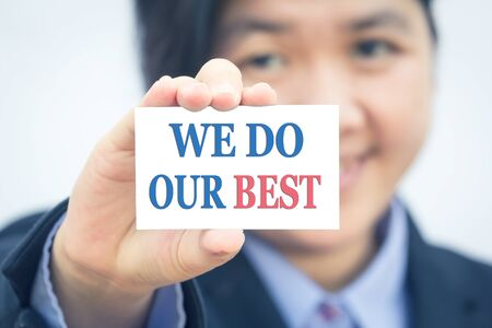 best message: Businesswoman holding card with WE DO OUR BEST message.