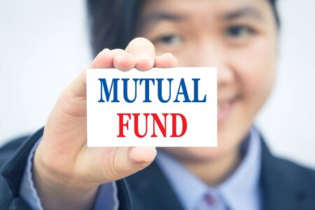 financial diversification: Businesswoman holding card with MUTUAL FUND message.