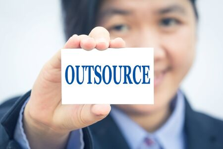 outsource: Businesswoman holding card with OUTSOURCE message.