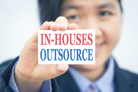 outsource: Businesswoman holding card with IN-HOUSE OUTSOURCE message. Stock Photo