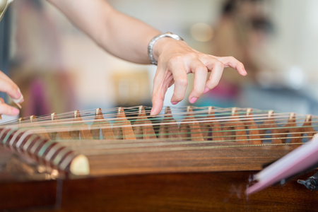 Hand of woman playing guzheng.