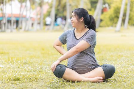rape: La mujer embarazada hacer ejercicio en el jardín preparar su cuerpo para entregar un niño. (Tono cálido) Foto de archivo