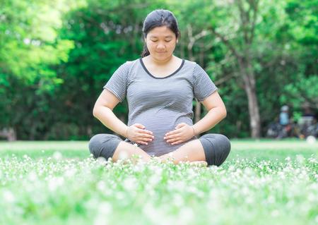 rape: La mujer embarazada sentada en el suelo llevar su vientre con cuidado y amor.