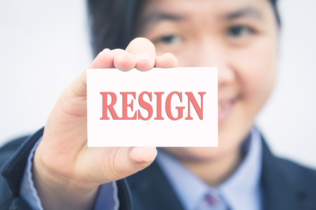 Businesswoman holding card with RESIGN message.