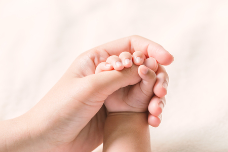 Baby hand holding finger mom on vintage tone. (Selected focus) Stock Photo