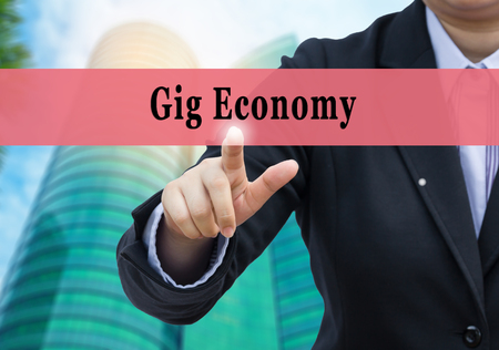 Businessman pointing to Gig Economy on blurr business building background. Stock Photo