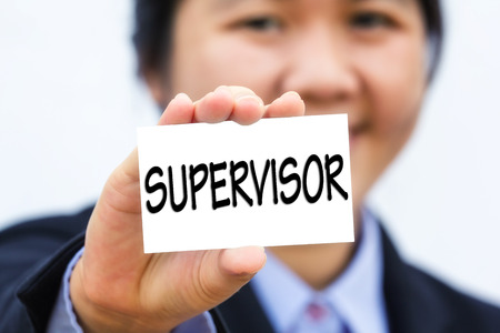 supervisor: Businesswoman holding card with SUPERVISOR message.