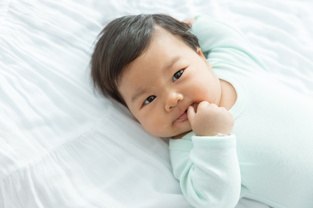 Adorable baby girl suck a finger on the bed. Standard-Bild