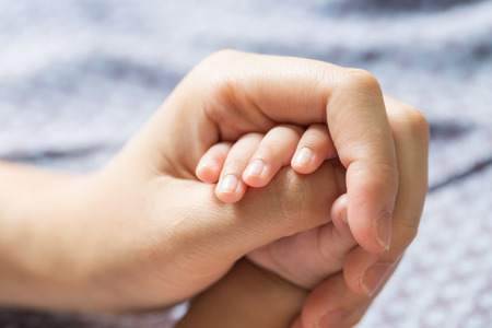 Baby hand holding finger mom. (Selected focus)