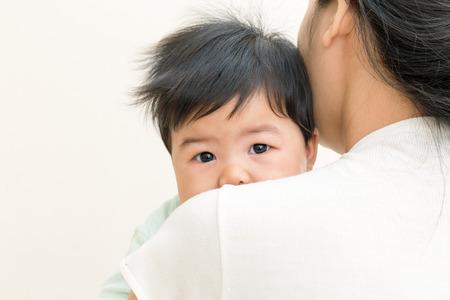 Schattige Aziatische baby ziek en ongelukkig op moeder schouder.