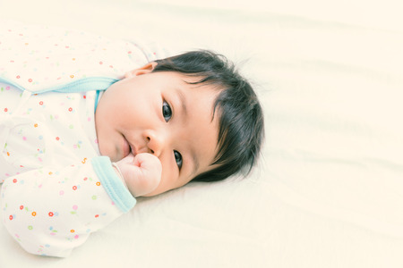 thump: Adorable asian baby sucking thump on the bed. (Warm tone)