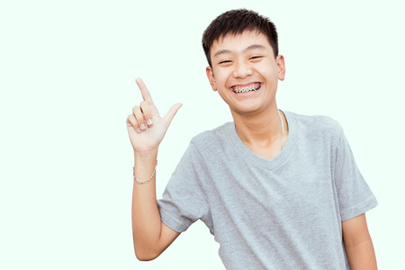 Beautiful smiling of handsome boy with teeth brace dental on isolated background. (Vintage tone) 版權商用圖片