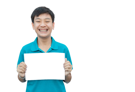 Asain teen beautiful smile teeth brace dental holding blank paper for texture on isolate background. Banco de Imagens