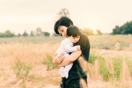 Asian woman holding her daughter for love or relation concept background. (Vintage tone)