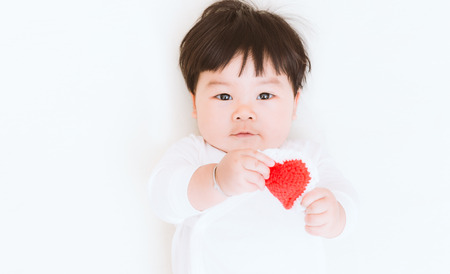 Asian baby cute girl show his love heart for valentine background. (Vintage tone)