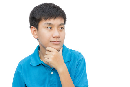 Teenage boy thinking and touch chin on isolate background. Stock Photo