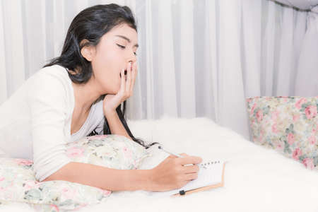 Beautiful woman tired and sleepy with notebook on living room. Can use for learning or business concept background.