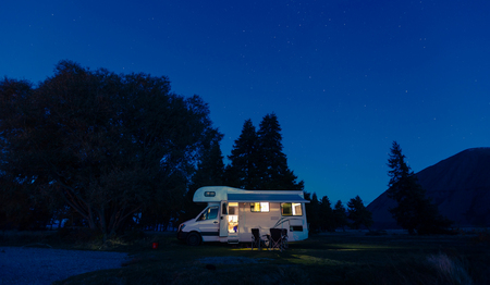 Motorhome on campsite at night. Can use for summer or holiday concept background. Stock Photo