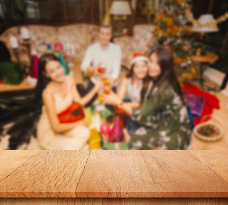 Plank wood or table top with blurred Friend or Family celebration christmas party background. Can use for display or marketing your product. Banco de Imagens