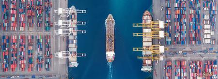 공중 전망의 탁 트인 유조선이 바다 항구 창고와 컨테이너 선박 또는 배달 컨테이너 선적을 위해 일하는 크레인 선박을 지나갑니다. 에너지 전력 또는 운송 또는 글로벌 물류 개념으로의 수출입에 적합합니다.