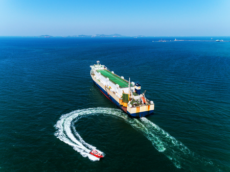 Aerial view Tug boats finish drag carry car ship or cargo ship to sea  for import  export or transportation concept background. Stok Fotoğraf
