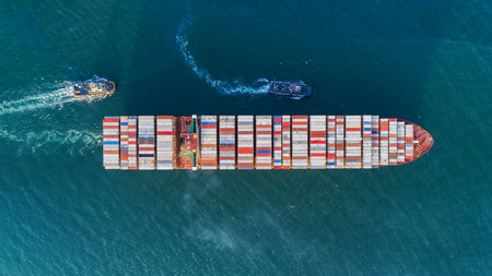Aerial view Tug boats drag container ship to sea port for unloading container at crane bridge for logistics import  export or transportation concept background. Фото со стока