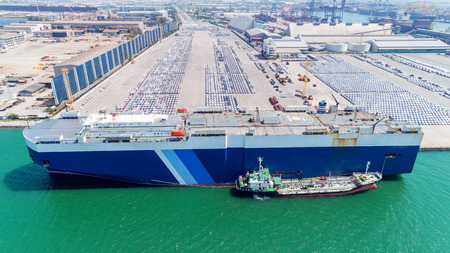 Aerial view carry car ship at car park in sea port or manufacture waiting for shipping export to worldwide. Standard-Bild