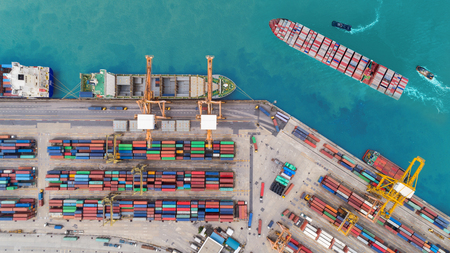 Aerial top view container ship at sea port and working crane bridge loading container for import export, shipping or transportation concept background. Stock Photo