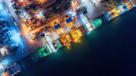 Aerial top view container ship at sea port and working crane bridge loading container for import export, shipping or transportation concept background. Stok Fotoğraf