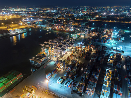 Aerial view container ship at container warehouse at sea port with working crane bridge loading container for import export, shipping or transportation.
