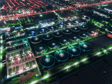 Aerial view water treatment plant at night with cityscape for environment concept. Stok Fotoğraf