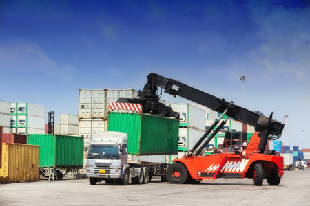 Forklift truck working in container warehouse with beautiful sky for logistics shipping, import export or transportation.