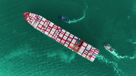 Aerial top view container ship and tug boat on the sea for import export, shipping or transportation concept background. Stok Fotoğraf