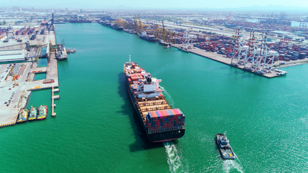 Aerial view Tug boats drag container ship to sea port and working crane bridge loading container for import  export, shipping or transportation concept background.