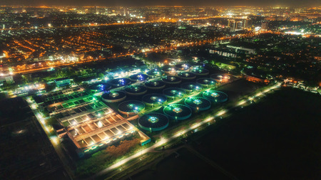 Aerial view water treatment plant at night with cityscape for environment concept. 版權商用圖片