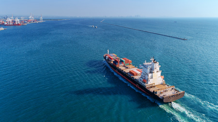 Aerial view container ship going to sea port for import export, shipping or transportation concept background.
