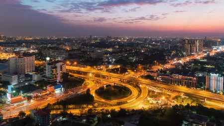 Aerial top view highway road intersection roundabout or circle with cityscape and beautiful sky for transportation, distribution or traffic background.