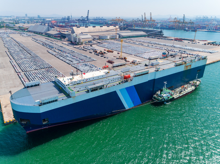 Aerial view of large RORO Vehicle carrier vessel parking for loading car at sea port.