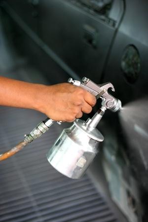 pulverizador: Mano con cuerpo de pistola y coche de pintura en aerosol