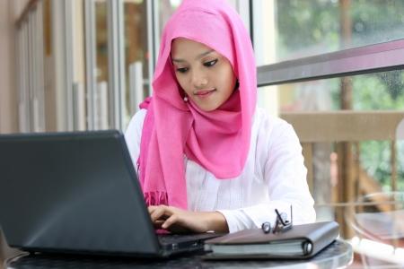 femme musulmane: Une jeune femme musulmane utilisant un ordinateur portable Banque d'images