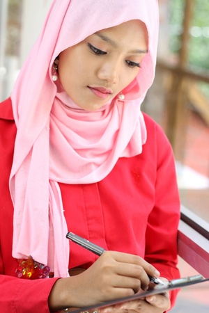 A young  muslim businesswoman writing a report file Imagens