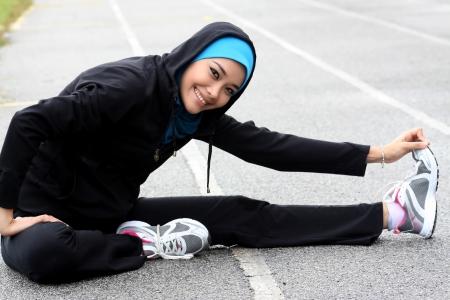 femme musulmane: Un athlète jolie femme musulmane qui s'étend de son corps à la piste du stade Banque d'images