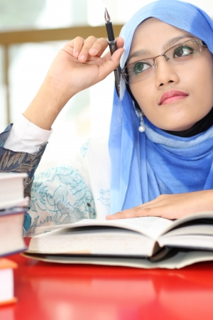 A young muslim girl reading a book while thinking photo