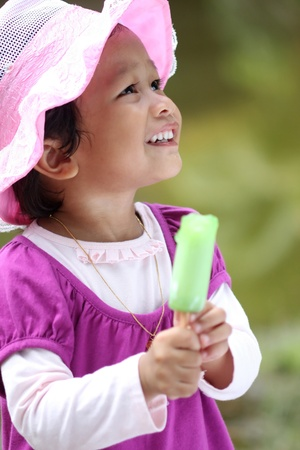 Little girls holding an ice cream while looking upstairs photo