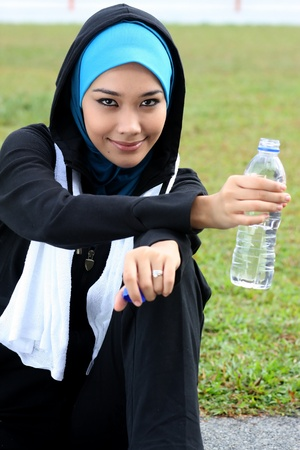 A muslim woman athlete holding a bottle of mineral water photo