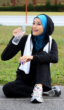 A pretty muslim woman athlete resting while drink a mineral water photo