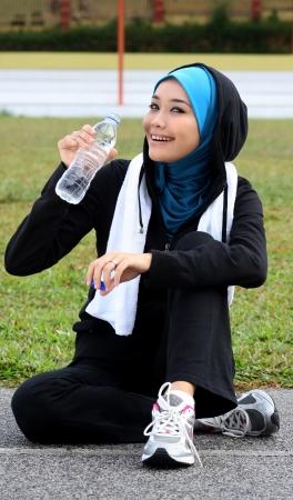 femmes muslim: Un athl�te jolie femme musulmane se reposer tout en boire une eau min�rale Banque d'images